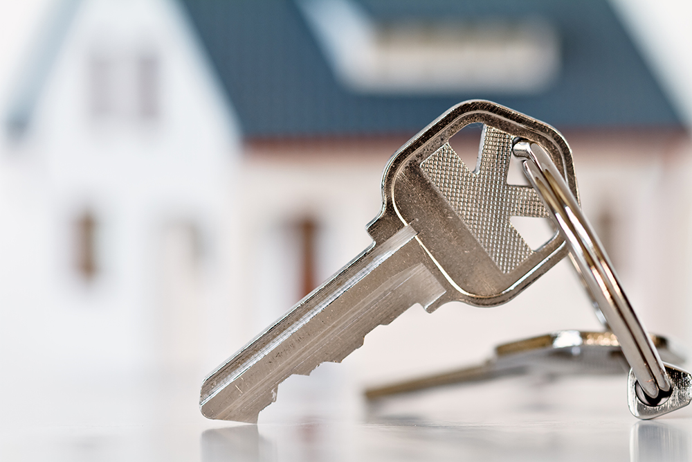 Keys in front of a house for sale after receiving thorough home inspection services