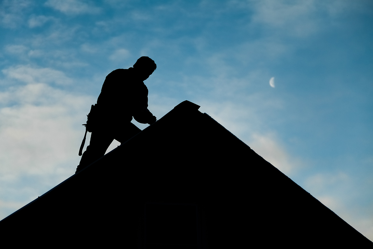 Silhouette of an inspector doing a home inspection on the roof