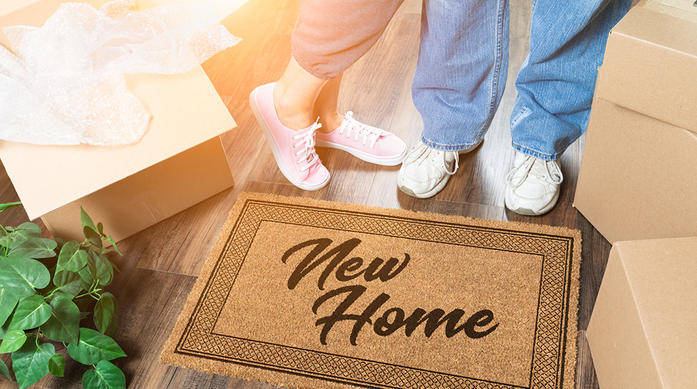 Couple standing next to a new house welcome mat surrounded by moving boxes after a home inspection